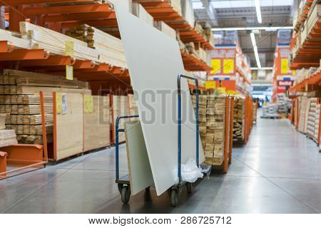 Construction Cart In The Building Store. Carts Loaded With Boards. Shop Of Building Materials. Racks