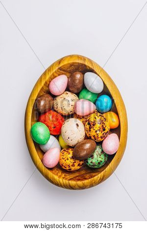 Sweet Sugary Easter Candy eggs in a wooden bowl on white backround. Top view poster
