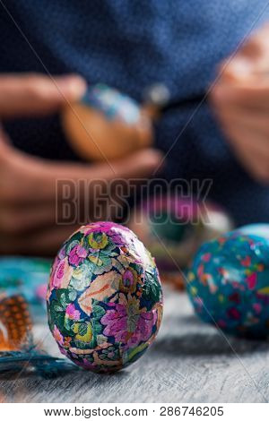 closeup of a young cacausian man decorating some homemade easter eggs by gluing some pieces of different papers, on a gray rustic wooden table poster
