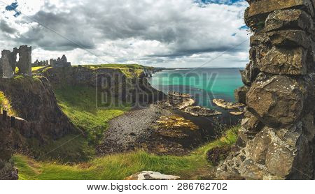 The overview from Dunluce castle to the Irish bay. Overwhelming Northern Ireland landscape. Epic shoreline view from above the cliff. The ruins of the Medieval building under the cloudy rainy sky.