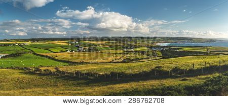 Countryside panoramic view of the green fields under the blue cloudy sky. Northern Ireland landscape. Stunning pastures of the English village. Picturesque grass covered land next to the shoreline.
