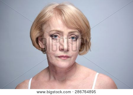 beauty portrait of mature woman face skin isolated ob blue background