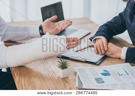 Cropped View Of Worker With Broken Arm Siting At Table With Documents Opposite Businessman In Office