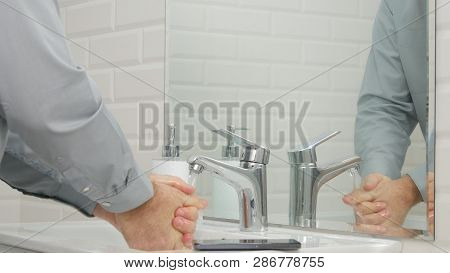 Image With A Businessperson In Office Bathroom Washing His Hands