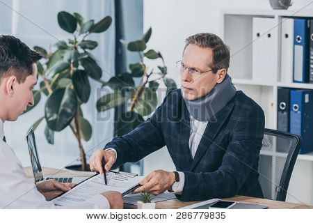 Businessman In Neck Brace Sitting At Table And Pointing On Form For Compensation Claim To Worker In