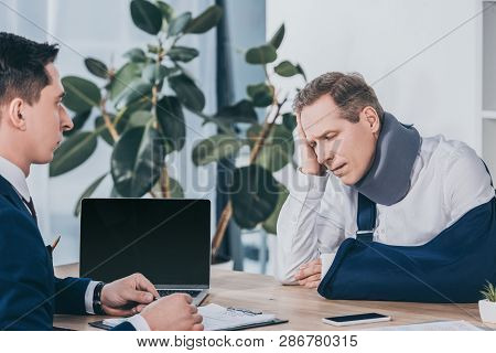 Upset Worker In Neck Brace With Broken Arm Sitting At Table Opposite Businessman In Blue Jacket In O