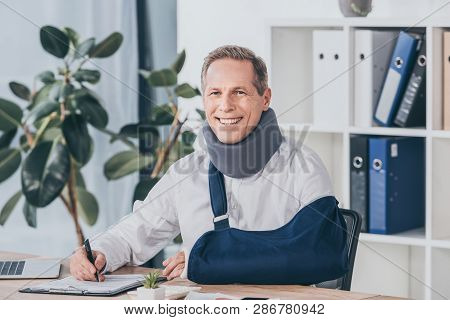 Worker In Neck Brace And Arm Bandage Sitting At Table, Smiling And Writing With Pen In Office, Compe