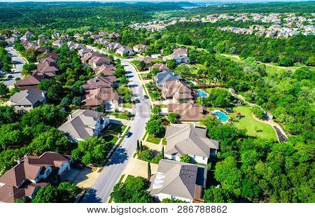 Cedar Park , Texas Aerial Drone View Above Texas Hill Country Homes On A Curved Road Leading Into Th