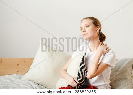 Woman Holds Pain Neck With Hand, Rubs And Massages. Concept Uncomfortable Mattress, Pillow, Bed. Hea