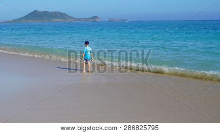 Boy Playing At The Beach And Getting His Feet Wet.