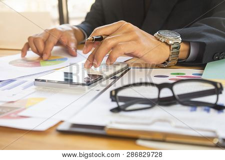poster of Business man in office and calculate financial plan sales. Working on desktop computer making business plan, business investment advisor consulting on the financial report, plan a marketing plan at business office. Business accounting plan concept.
