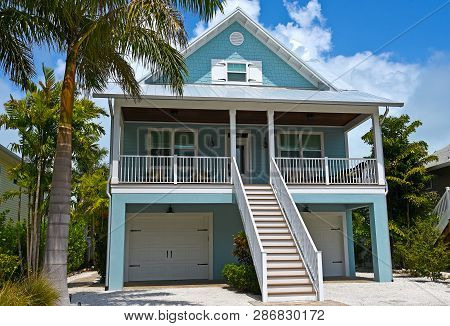 Beach House With Deck, Garages And Beautiful Landscaping Including Palm Trees