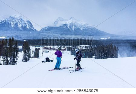 Unidentifiable Skiers And Snowboarders Descend The Snowy Mountain Slopes At Lake Louise Inside Banff