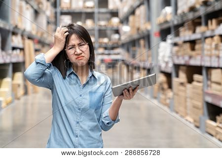 Young Unhappy Asian Woman, Auditor Or Employee Looking And Feeling Confused In Warehouse Store. Port
