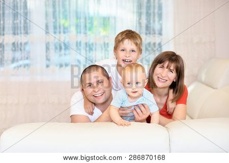 The Concept Of The Family, Young Parents With A Baby And His Brother, Happy Childhood. The Family On
