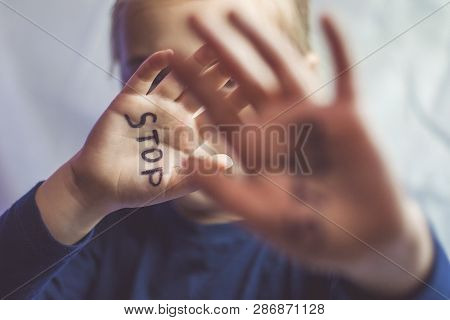Concept Of Domestic Violence And Child Abusement. A Little Girl Shows Her Hand With The Word Stop Wr