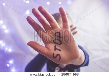 Little Frightened Girl Shows The Word Stop Written On The Arm. Children Are Subjected To Violence An