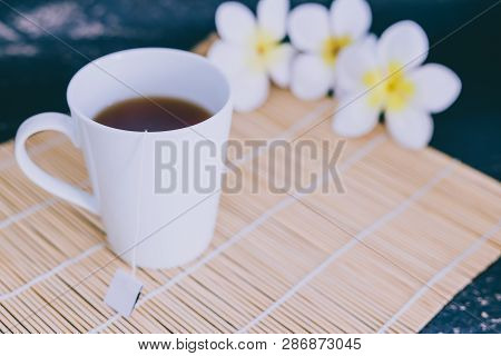 Cup Of Dark Tea On Bamboo Placemat With Spoon And Flowers All Around