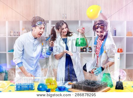 Group Of Excited Young Scientists Making Experiment In Modern Laboratory.