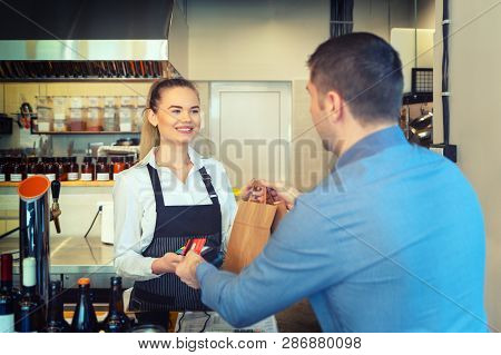 Man Paying Takeaway Order By Credit Card On Reader Holded By Smiling Waitress Working At Shop Counte
