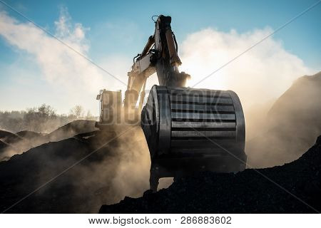Yellow Big Excavator In The Coal Mine, Loads The Breed, With The Bright Sun And Nice Blue Sky In The