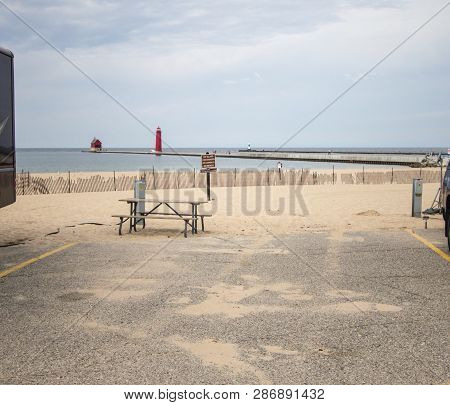 Campsite On The Beach. Beautiful lakefront campsite on a sandy beach with a red lighthouse at the horizon on the coast of Lake Michigan. Grand Haven State Park, Michigan. poster