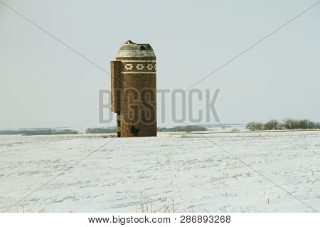 A Abandoned Silo Out In A Field On A Snow Covered Ground.