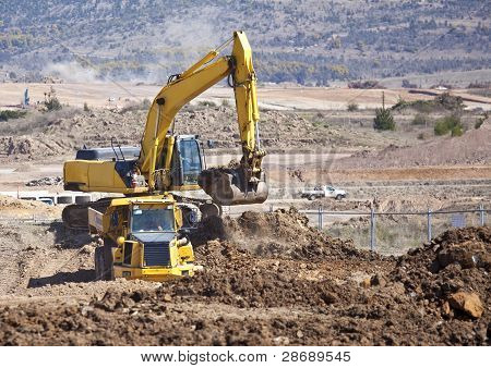 Earth moving machine loading soil into truck