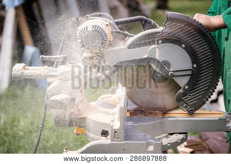 Master carpenter at work in the workshop outdoors. Carpenter hand sawing wood with table wood cutter saw poster