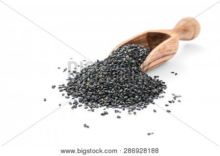 Black organic sesame seeds in wooden scoop on white background