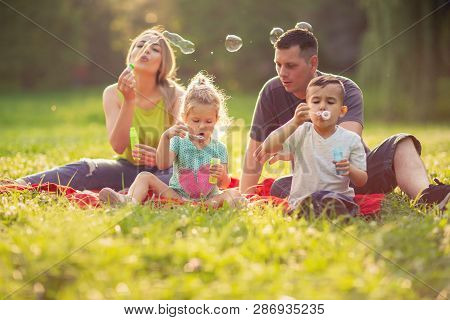 Happy Young Family In The Park On A Sunny Day Blow Soap Bubbles.