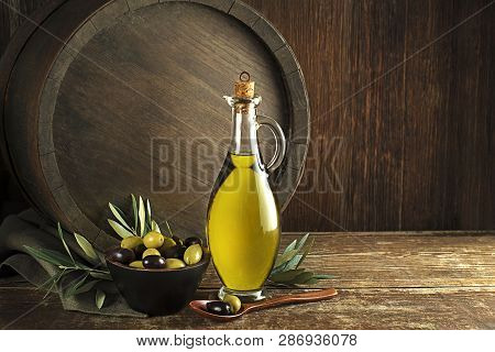 Bottle Of Extra Virgin Healthy Olive Oil With Barrel Background