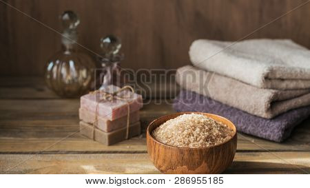 Sea Salt, Natural Handmade Soap, Natural Cosmetic Oil And Colorful Towels On Rustic Wooden Backgroun