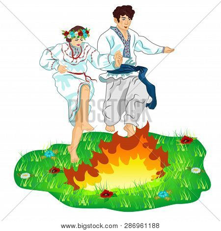 Young Guy And Girl In Ukrainian Traditional Clothes Leap Across A Bonfire On A Flower Lawn. The Cele
