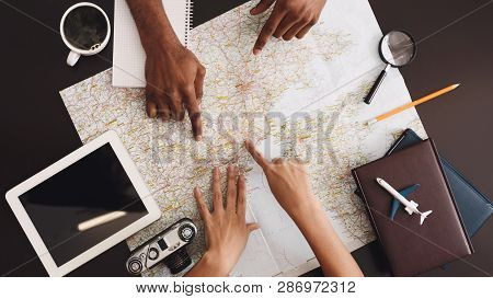 Planning Trip. Couple Discussing Tour Plans Using Map, Top View