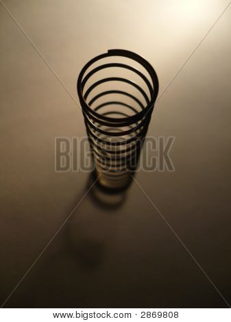 Metal spring on the sheet of paper poster