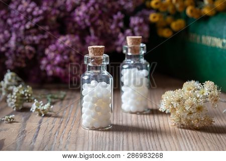 Bottles Of Homeopathic Globules With Dried Herbs And A Materia Medica, I.e. A Book Of Remedies And T