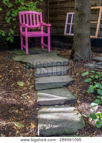 Snug place in the old garden with pink wooden chair