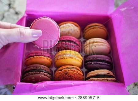 Colorful French Macarons In A Box With A Hand Holding One.