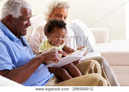 Grandparents Sitting On Sofa At Home With Baby Granddaughter Reading Book Together poster