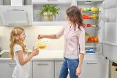 Beautiful, young woman pouing orange juice with pitcher. Pretty, cute girl holding glass and smiling. Mom and daughter standing near refrigerator with healthy, eco foodstuff. poster