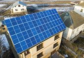 Aerial view of new modern two story house cottage with blue shiny solar photo voltaic panels system on the roof. Renewable ecological green energy production concept. poster