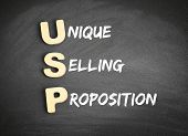 Wooden alphabets building the word USP - Unique Selling Proposition acronym on blackboard poster