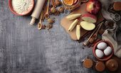 Cooking home baking. Homemade foodstuffs on dark wooden kitchen table with raisins,  and apples. Traditional dessert . Flat lay food background. Top view. poster