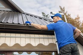 Man Standing On Ladder And Cleaning Roof Rain Gutter From Dirt