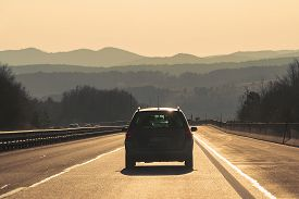 Car Travel In Highway. Traveling By Car On The Road. Car In Highway Landscape In Sunset. Travel By C