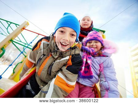 Happy kids in winterwear playing outside on playground