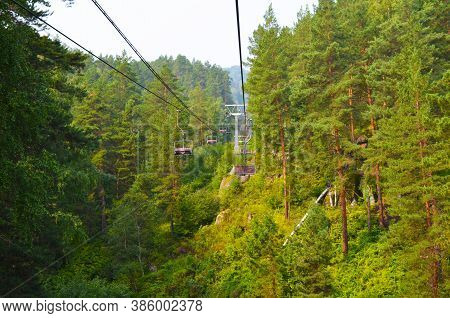 Suspended Cable Car In The Summer Forest. Climb The Mountain. Nature