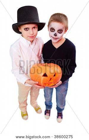 Photo of two eerie boys with Halloween pupkin looking at camera