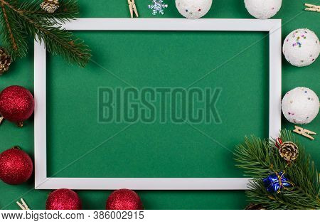 White Frame With Fir Branches And New Year's Toys On A Green Background. Christmas Card